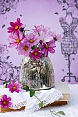 Bouquet of pink cosmos in silvered glass vase