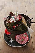 Arrangement of Christmas decorations and moss in black dish and hand-crafted paper rosette on plate