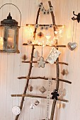 Aus Ästen selbstgebaute Weihnachtsleiter als Weihnachtsbaum mit Lichterkette