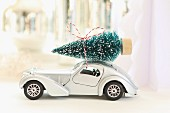Toy car with Christmas tree on roof against blurred background