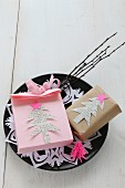 Hand-made, pink paper bag and gift decorated with paper Christmas trees on plate with doily and twigs