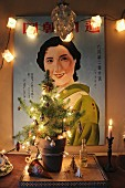 Small, decorated Christmas tree with fairy lights in front of illuminated poster of Japanese woman