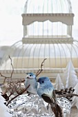 Two bird ornaments on crystal bowl in front of vintage bird cage