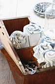 Rolled tea towels and vintage perforating tools in old wooden box with open lid