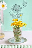 Yellow wildflowers in glass on saucer in front of green canvas printed with floral pattern; row of green beads in foreground
