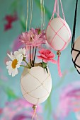 Small flowers in blown Easter egg in macrame holder
