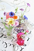 Still-life arrangement of colourful wildflowers in various glasses on printed fabric