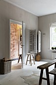 Living room with walls painted pale grey and view of brick wall through open door