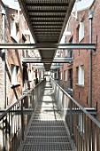 Langer Gang aus Gitterrost mit Zugängen zu den Wohnungen
