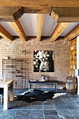 Wood-beamed ceiling, brick wall, large photo, bench and cowhide rug on slate floor in loft apartment