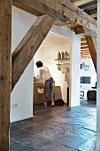 Exposed wooden beams and slate floor in loft apartment with woman in kitchen in background