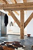 Rustic wooden beams and cowhide rug on slate floor