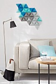 A decorative wall hanging made from homemade tetrahedrons, cut from coloured paper above a sofa