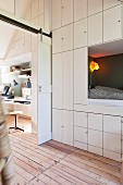 Floor-to-ceiling fitted cupboards, cubby bed and desk in child's attic bedroom