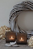 Lit tealights in smoked glass tealight holders in front of wicker wreath painted pale grey