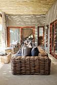 Sofa mit grobem Rattangestell auf grau getönter Veranda und entrindeter Holzabdeckung