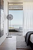 Open balcony door in modern bedroom