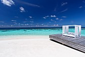 Sofa with awning on wooden jetty on sandy beach (Maldives)