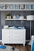 White baby-changing cabinet against grey-striped wallpaper and alphabet frieze in nursery