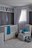 Striped, grey armchair next to cot in nursery with blue accents