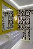 Moderner Waschtisch mit länglichem Aufsatzbecken und geschliffenem Spiegel auf senfgelber Wand, im Hintergrund klassische schwarz-weisse Tapete