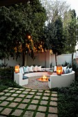Cosy, circular, masonry bench with lanterns on backrest and many cushions around hearth in twilit garden