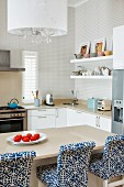 Bar stools with blue and white patterned upholstery at breakfast bar in modern kitchen area