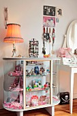 Display case decorated with pink toys, jewellery and table lamp in vintage-style girl's bedroom