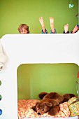 Kinder auf Etagenbett vor grün getönter Wand