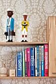 Tapezierte Wand mit heller Musterung als Hintergrund für Bücher und Figuren auf einem Wandbord
