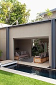 Narrow pool between lawn and open-sided seating area with sofas