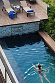 Woman swimming in pool below wooden deck with sun loungers
