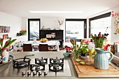 View past flowers and gas hob on island counter into dining area of houseboat