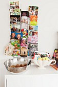 Postcards and family photos in card rack and business cards in soup tureen