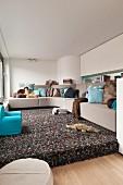 Kleines Wohnzimmer in Braun und Blau, Ecksofa auf einem Podest mit Hochflorteppich