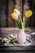 Yellow tulips in small ceramic vase