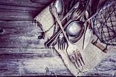 Angelaufenes antikes Silberbesteck und Drahtkorb auf einem Stück Leinen