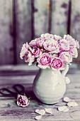 Ein Strauß rosa Rosen in Keramikkrug, daneben einzelne Blüte und Blütenblätter