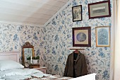 Floral wallpaper and old, framed photos above valet stand in attic bedroom