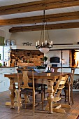 Rustic dining table, wooden chairs and candle chandelier in kitchen with wood-beamed ceiling
