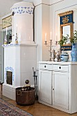 Simple, white-painted cabinet next to fireplace with blue and white tiles in rustic interior