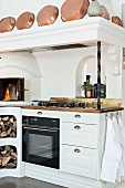 White, country-house-style kitchen counter with integrated oven, fireplace, firewood store and copper pans on mantel hood