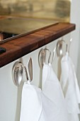 Tea towels hanging from dessert spoons bent into hooks