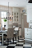 White and grey country-house kitchen with chequered floor and dining set below chandelier
