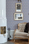 Rococo armchair with gilt frame next to rounded, tiled corner fireplace and against blue-patterned wallpaper