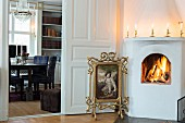 Tapestry fire screen in ornate gilt frame between open fire and open door with view into dining room