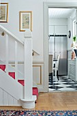 White-painted wooden staircase in hallway and open door with view of stainless steel fridge in kitchen