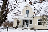 Renovated country house with white wooden veranda and balcony seen from wintry garden