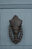 Vintage metal door knocker with head motif on door painted blue grey