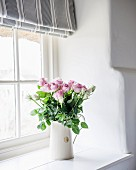 White jug of pink roses on windowsill